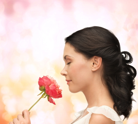 nature and beauty concept - smiling woman smelling flower with eyes closed