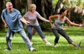 Multi-ethnic group of adults practicing tai chi in park.  Main focus on senior man (60s).